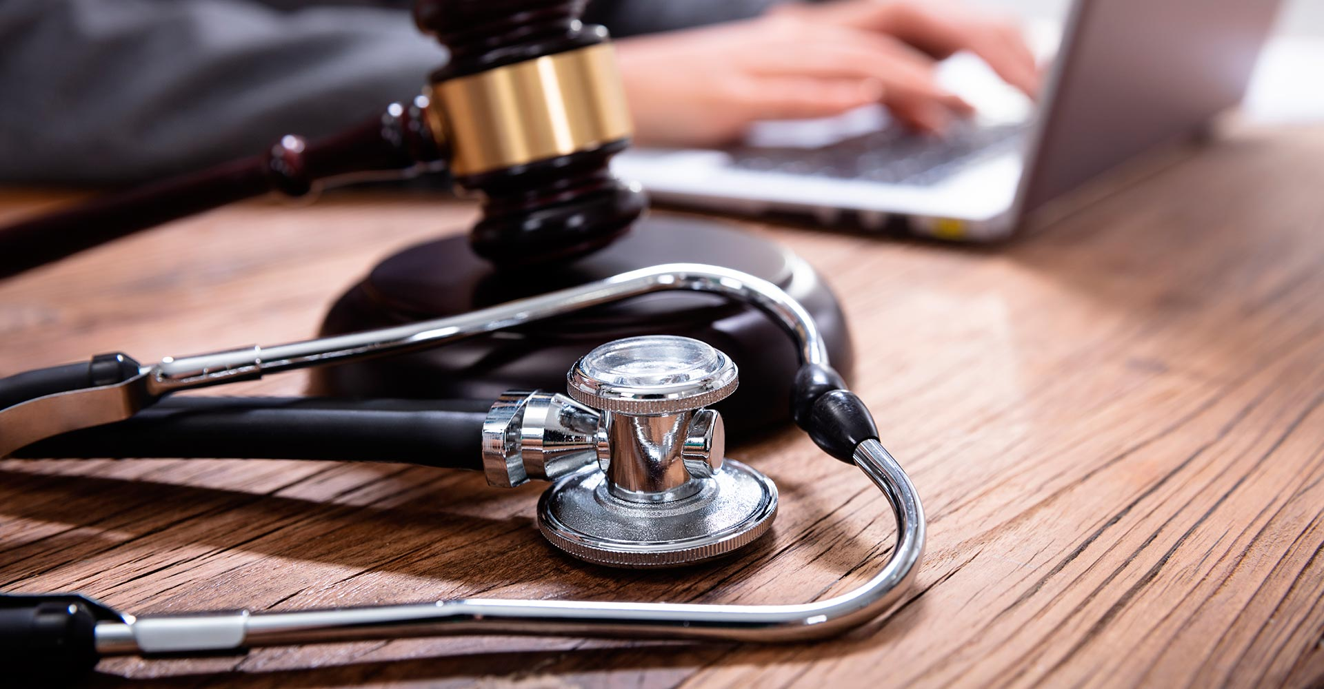a stethoscope and judge gavel on a desk of an attorney working on a malpractice case
