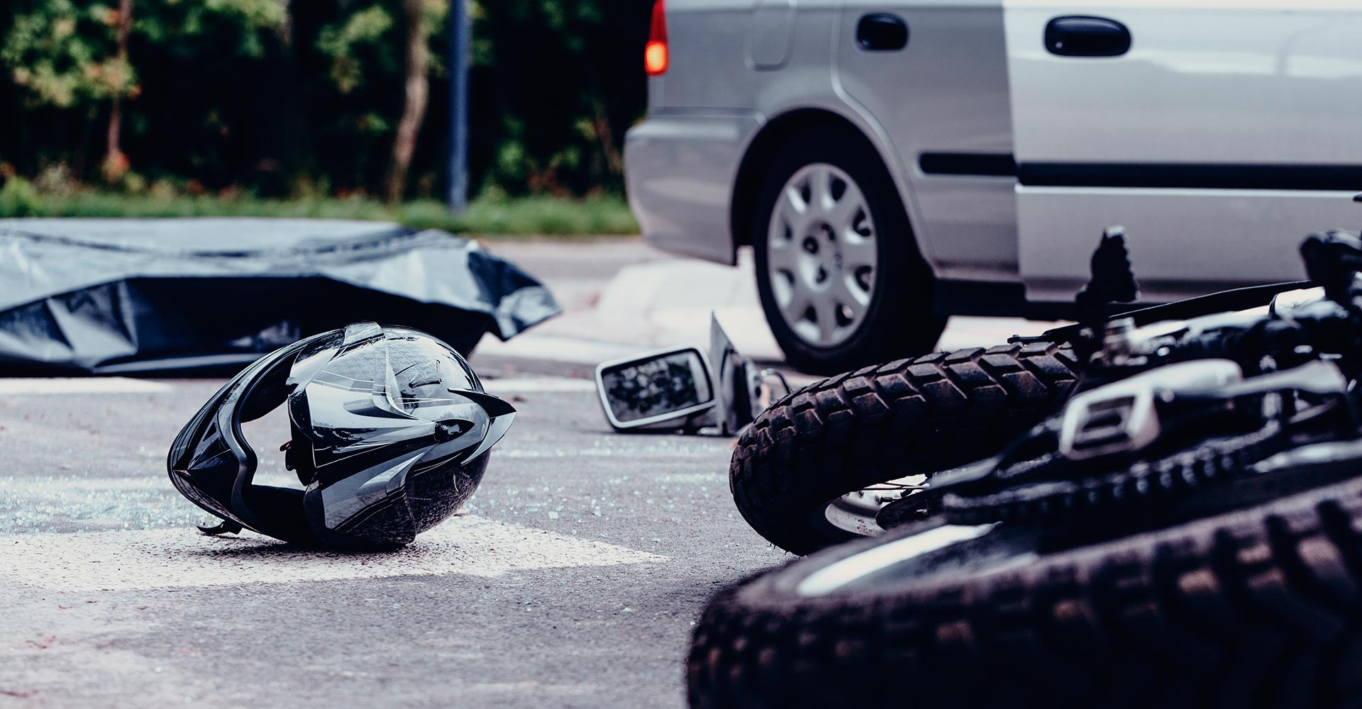 a helmet and a motorcycle lying on the road after a crash with a car