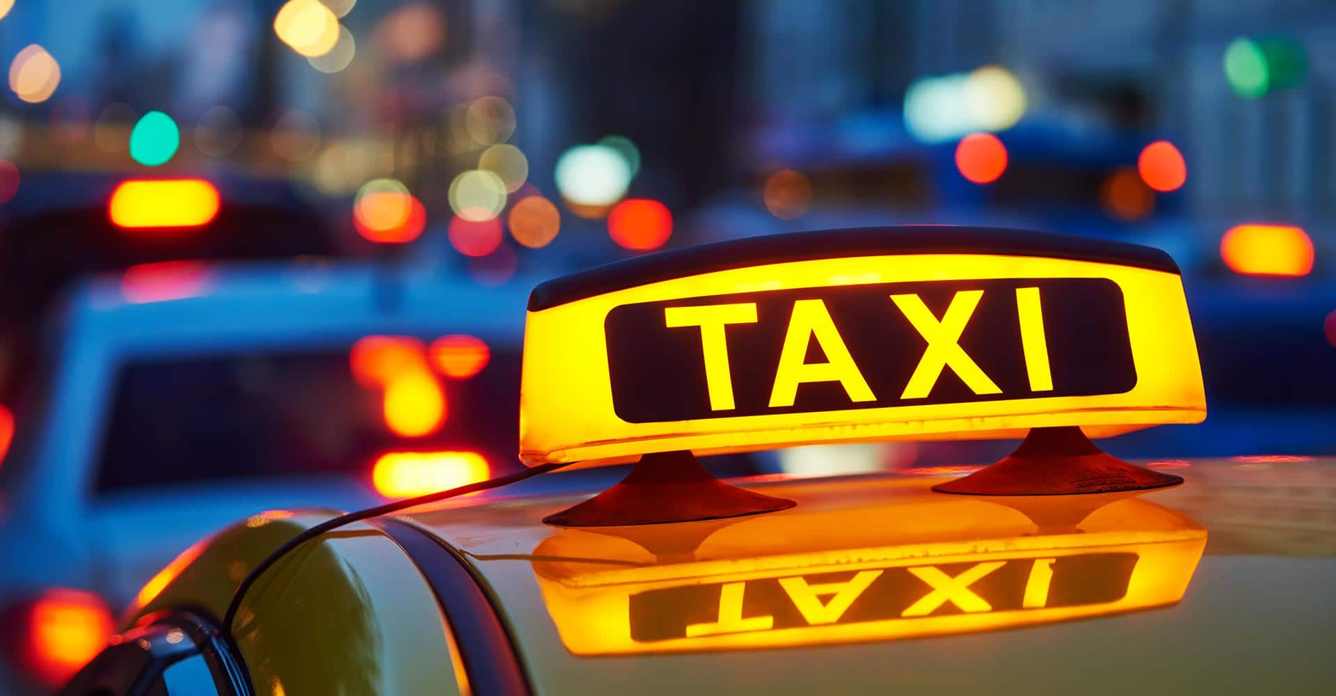 yellow taxi sign on cab car at evening or night in the city street