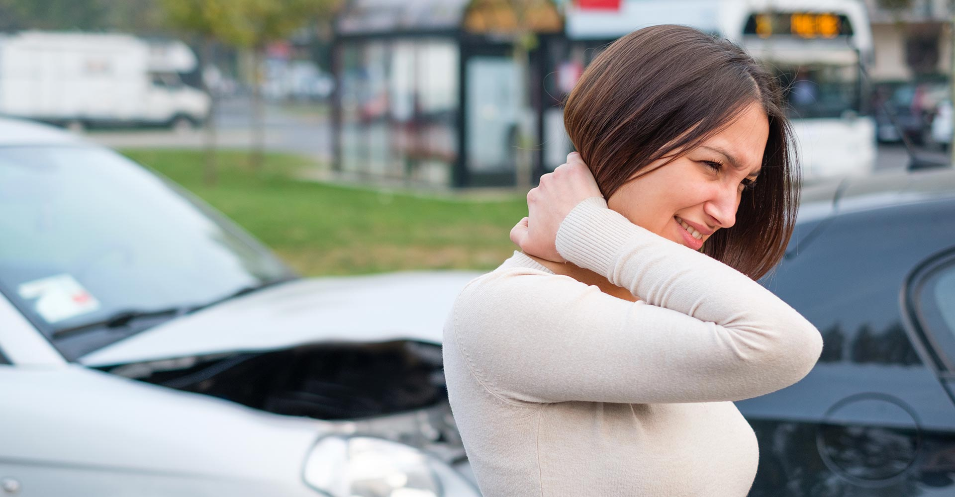 Woman feeling pain and whiplash after cars pileup